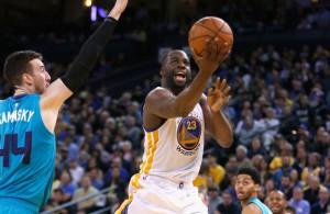 Draymond Green von den Golden State Warriors legt den Ball gegen die Charlotte Hornets in den Korb.