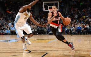 CJ McCollum von den Portland Trail Blazers dribbelt mit Ball an seinem Gegenspieler von den Denver Nuggets vorbei.