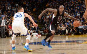Jamal Crawford von den Los Angeles Clippers zieht mit dem Ball in der Hand an Steph Curry von den Golden State Warriors vorbei.