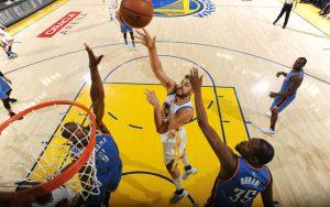 Andrew Bogut von den Golden State Warriors setzt sich unter dem Korb gegen zwei Gegenspieler der Oklahoma City Thunder durch.