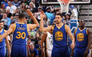 Steph Curry, Klay Thompson und Draymond Green von den Golden State Warriors klatschen sich während eines NBA-Spiels ab.