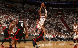 Dwyane Wade von den Miami Heat geht im NBA-Spiel gegen die Toronto Raptors gegen drei Verteidiger zum Sprungwurf hoch.