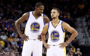 Kevin Durant und Steph Curry von den Golden State Warriors beraten sich in einer Spielpause.