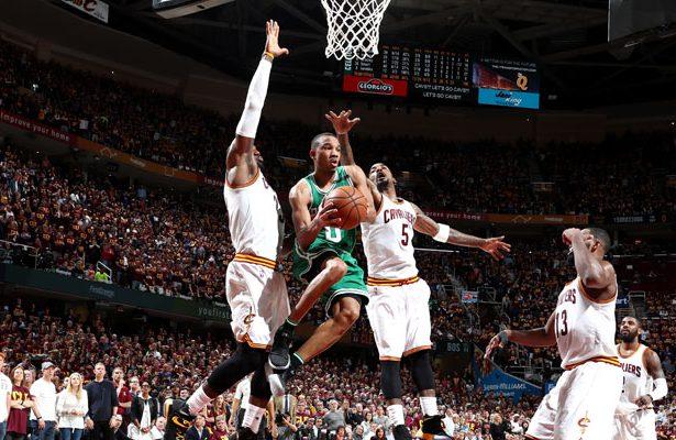 Avery Bradley von den Boston Celtics wird im NBA-Spiel von drei Gegenspielern beim Korbleger gestört.